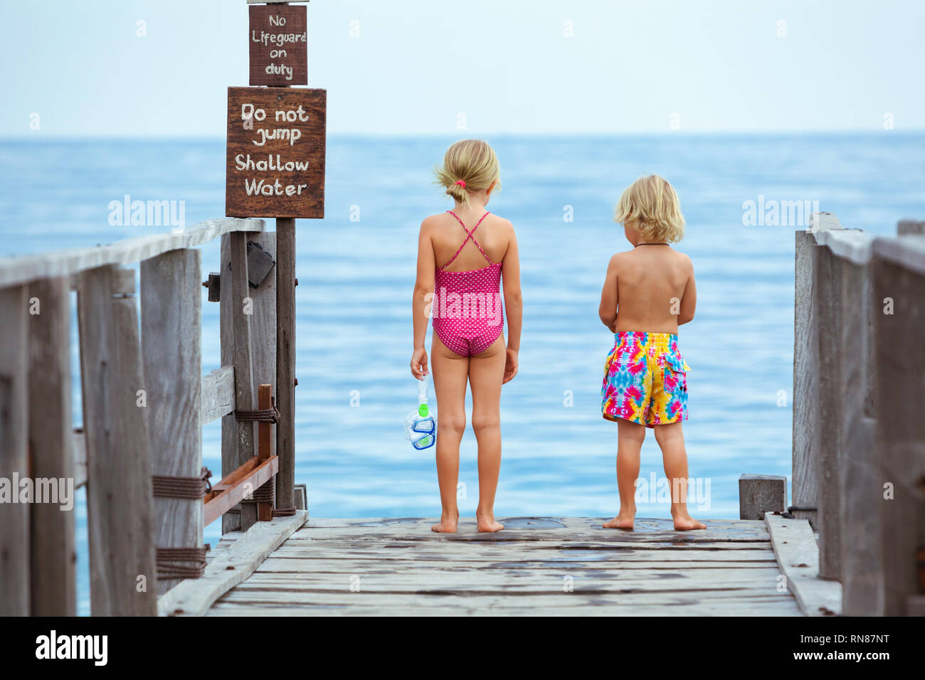 Happy little children with snorkeling masks going to dive in tropical sea pool to exploring underwater nature. Travel lifestyle, water sport, swimming - Stock Image