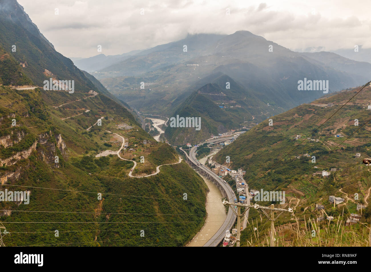 highway passes in a gorge in the mountains along the river, Heng River, Yunnan Province, China - Stock Image