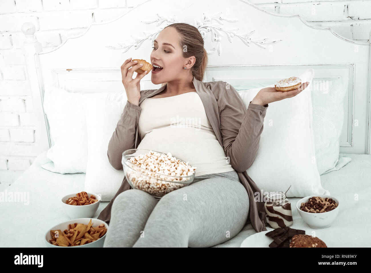 Cheerful thick woman lying in bed and filling herself with junk food - Stock Image