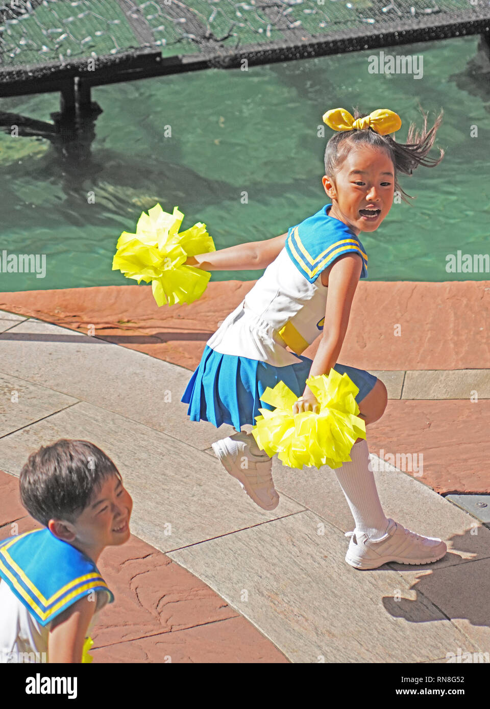 Boy and girl cheerleaders entertaining at Canal City shopping center - Stock Image