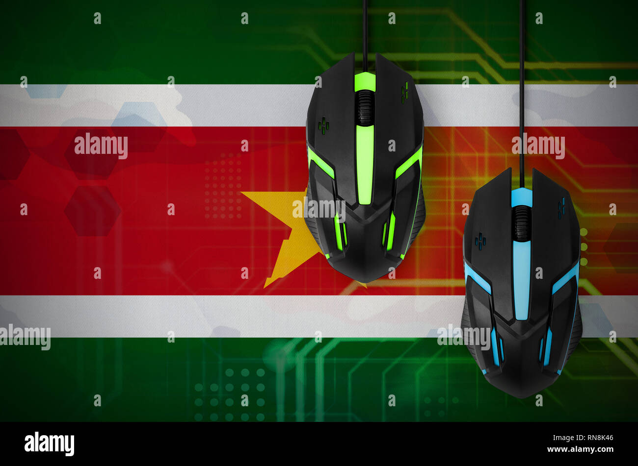 Suriname flag  and two modern computer mice with backlight. The concept of online cooperative games. Cyber sport team - Stock Image