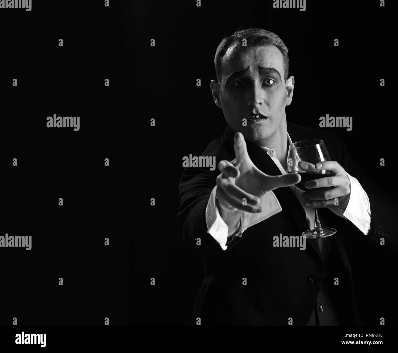 Where are you. Stage actor pantomime drinking wine. Comedian with mime makeup hold wine glass. Mime artist perform on stage. Drama theatre actor - Stock Image