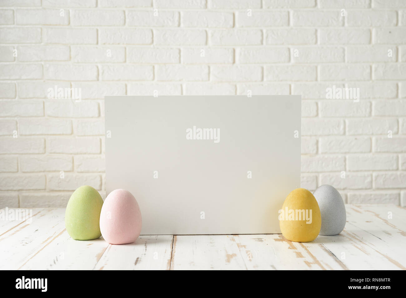 Easter composition with eggs, white board against white bricks wall Stock Photo