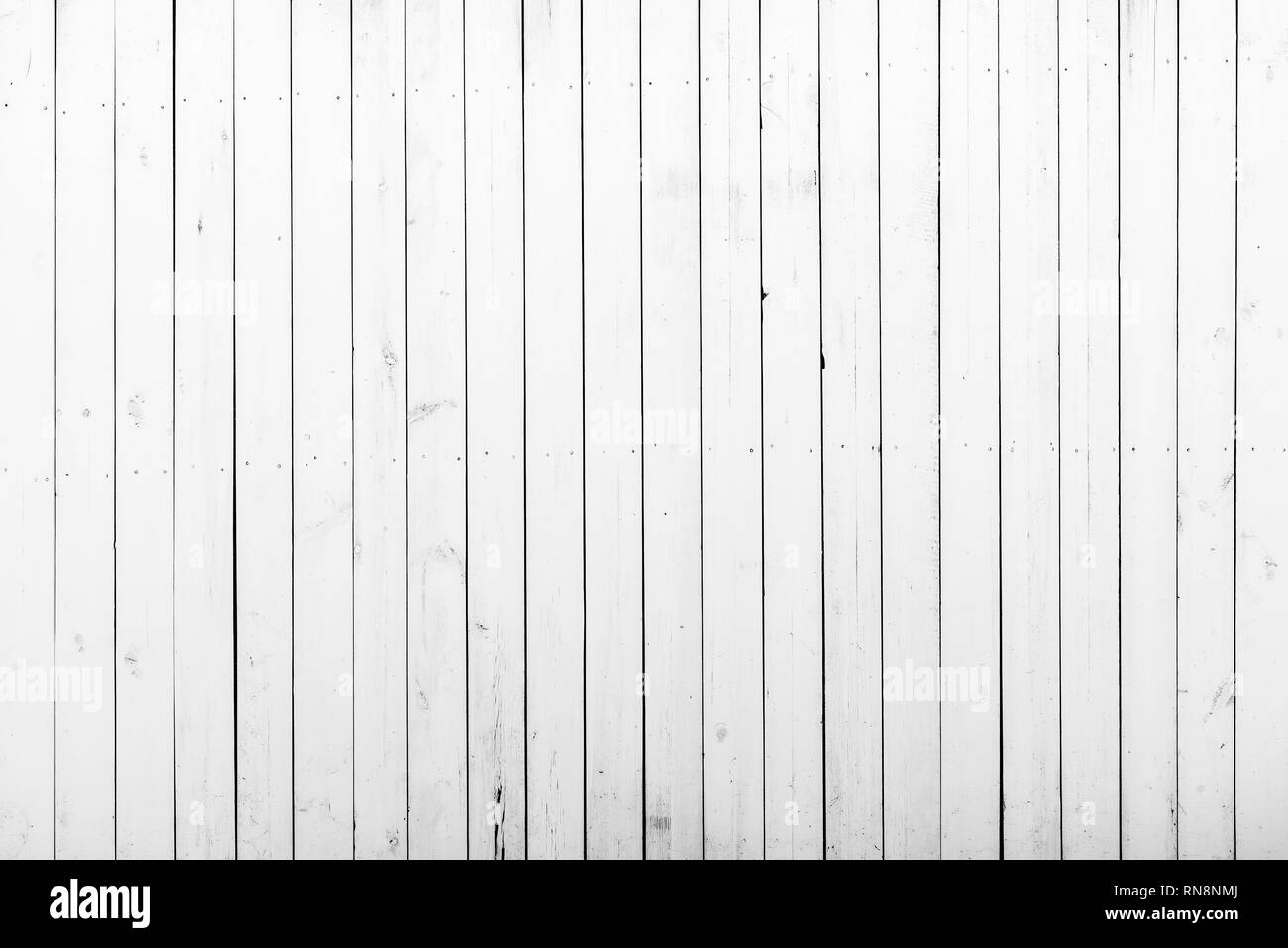 White wooden wall with a lot of cracks, knots and nails. Weathered timber planks, messy and dust, background with rich texture - Stock Image