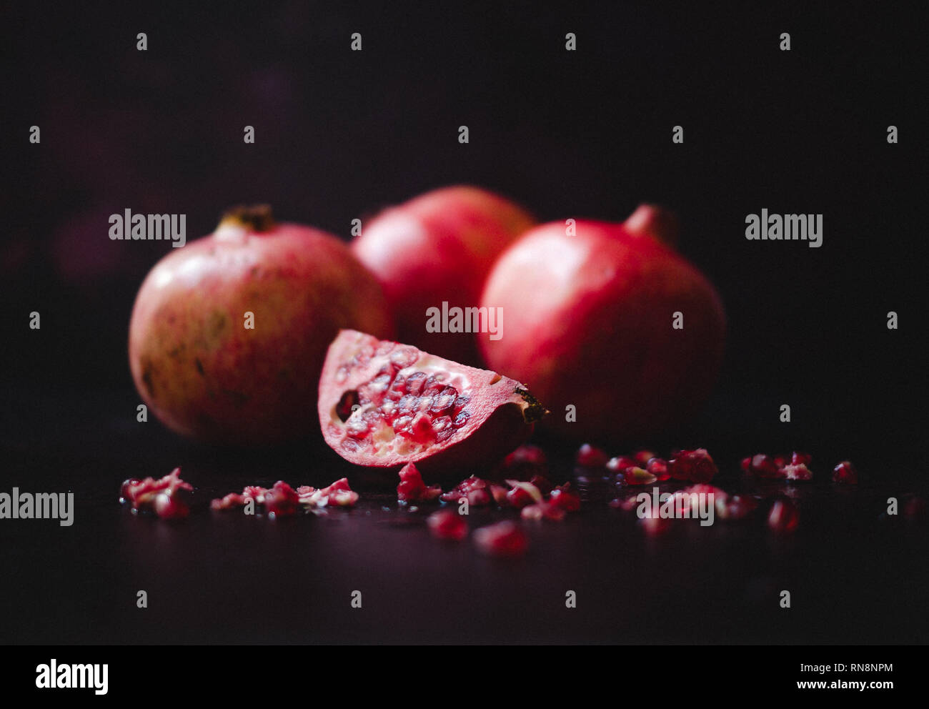 Still life of pomegranates in a Dutch Masters style, shot in natural light. The fruit has been sliced open to reveal the gem-like seeds within. - Stock Image