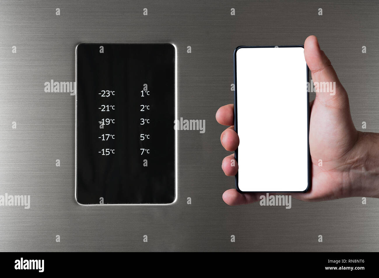 Hand holding frameless smartphone near fridge and freezer control panel. Internet of things abstract concept. - Stock Image
