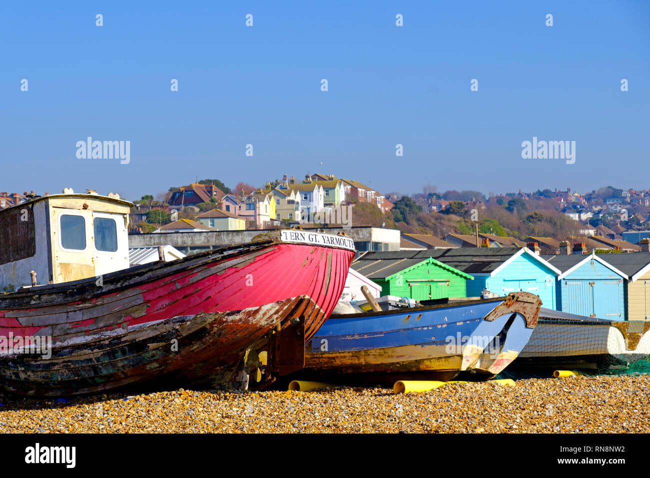 Old fishing boats and beach huts on the Bulverhythe beach, West St Leonards, East Sussex. UK Stock Photo