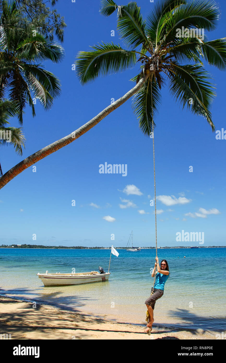 Young woman swinging on a rope swing at Pangaimotu island near Tongatapu island in Tonga. Kindom of Tonga is an archipelago comprised of 169 islands - Stock Image