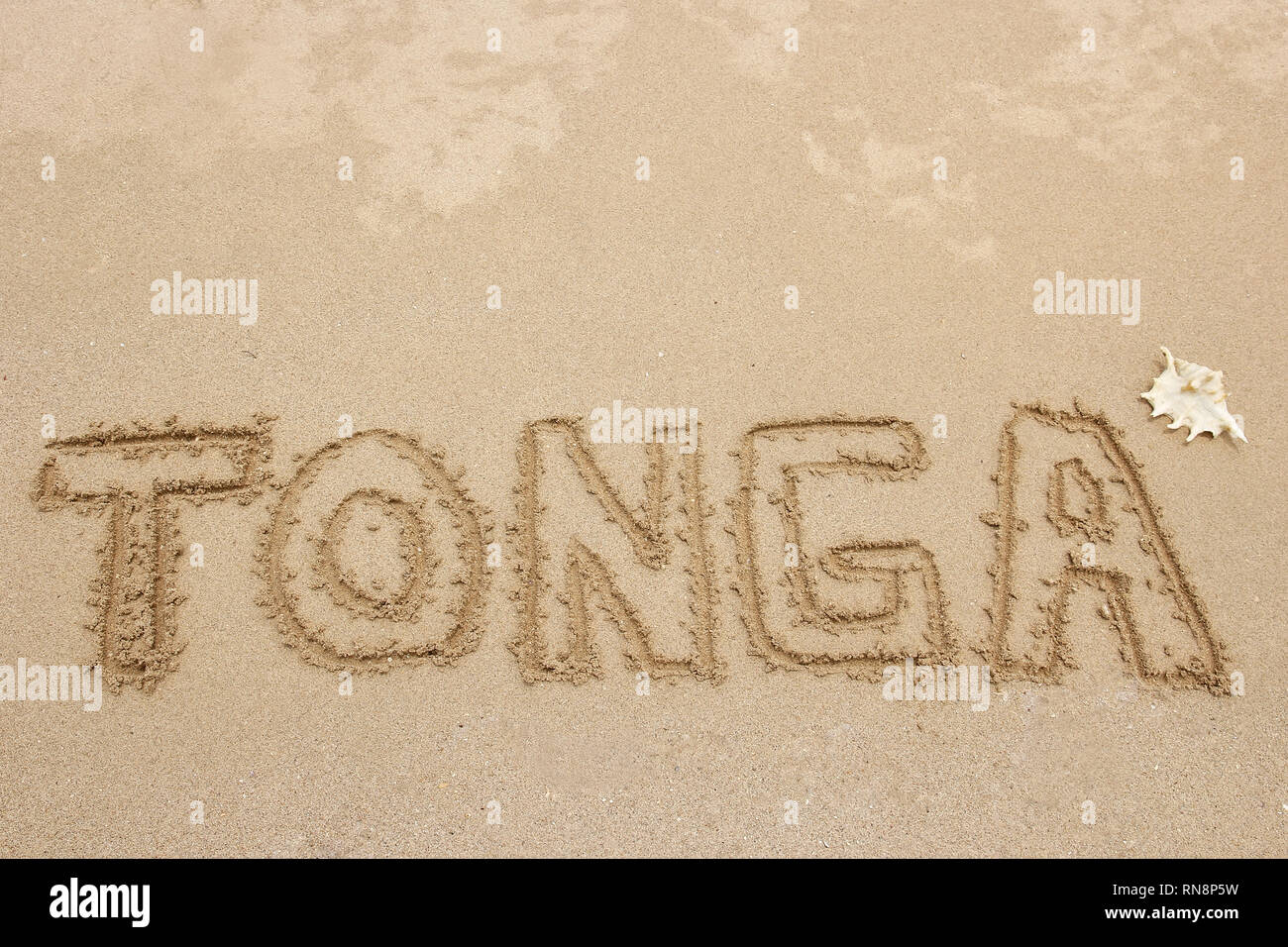 "Word ""Tonga"" written in a sand - travel concept Stock Photo"