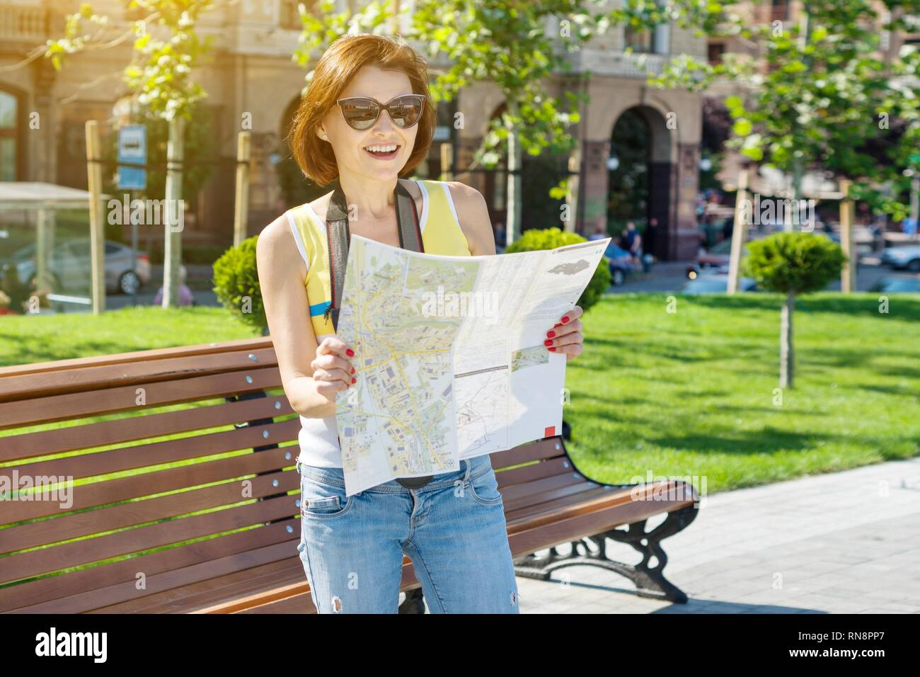 Happy woman tourist travel holding camera and map. Background of the European city - Stock Image