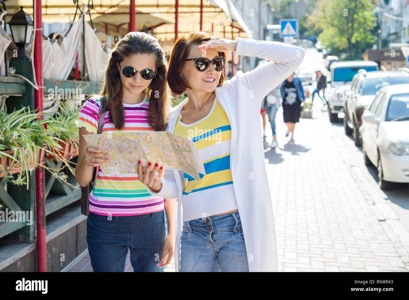 Mother and teen daughter on city street look at the map. Traveling Family - Stock Image