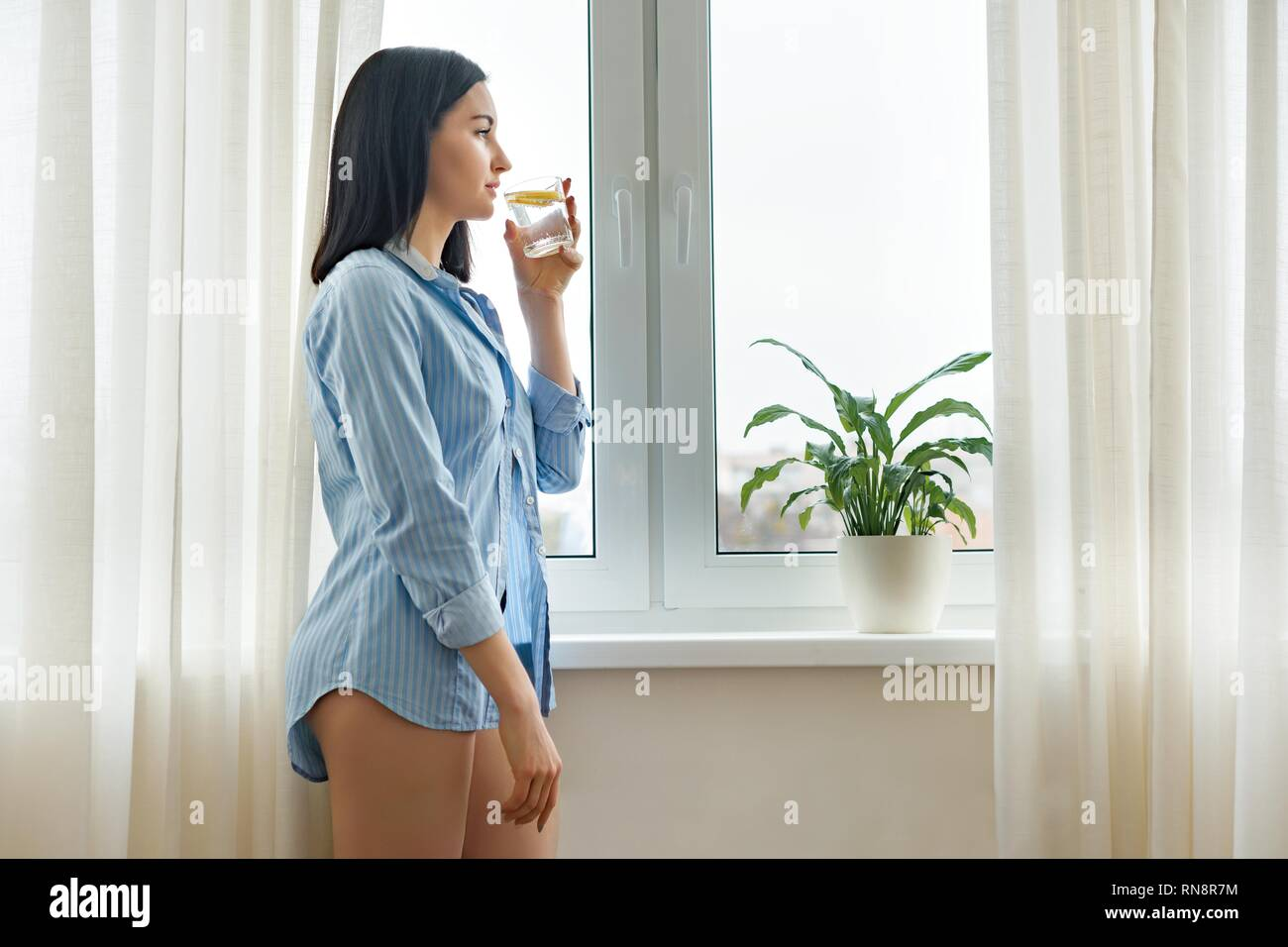 Healthy lifestyle, diet, antioxidant. Morning glass of water with lemon in the hands of young woman - Stock Image