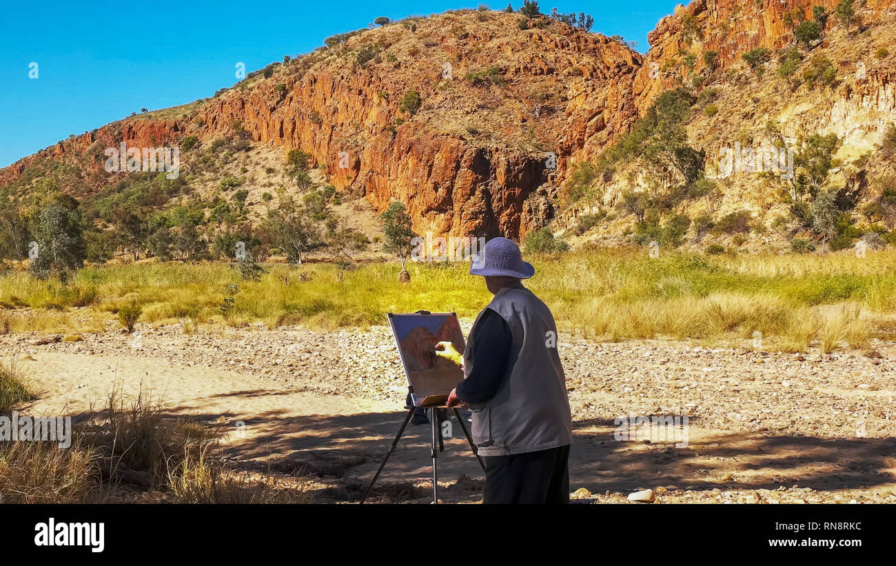 an artist paints glen helen gorge in the west macdonnell ranges near alice springs - Stock Image