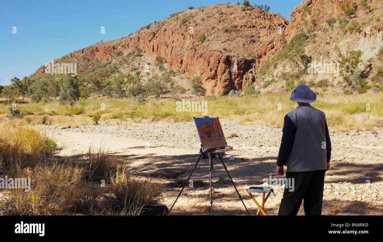 an artist steps back and contemplates her painting of glen helen gorge in the west macdonnell ranges near alice springs - Stock Image