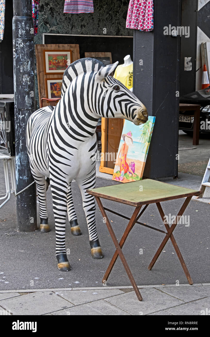 A sculpture of a zebra stands outside a secondhand shop in the Stokes Croft area of Bristol, UK. - Stock Image