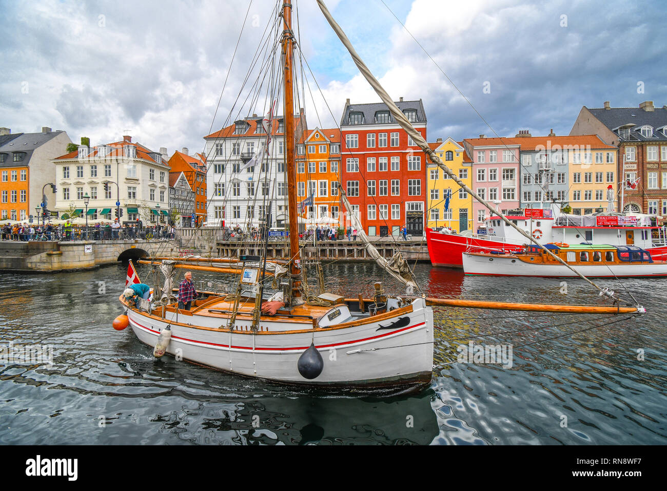 A senior man and woman dock their sailboat on the canal on an overcast day in the colorful 17th century Nyhavn district in Copenhagen, Denmark. - Stock Photo