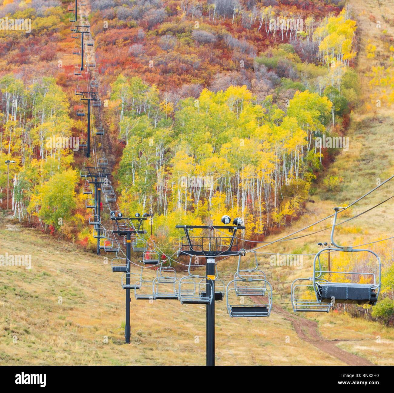 empty mountain ski lift amid lush trees with vivid autumn colors near Park City, Utah - Stock Image