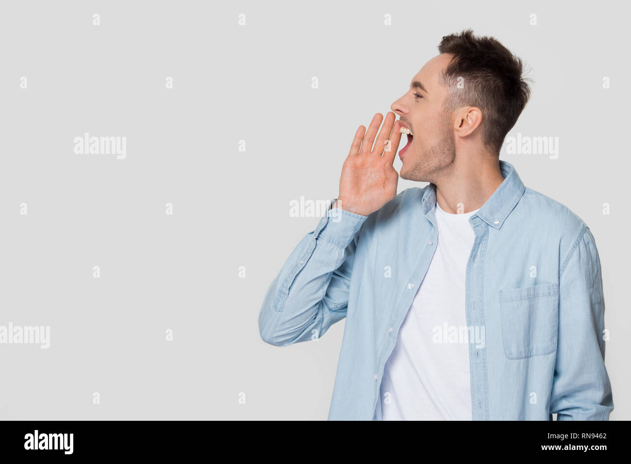 Young man shouting at copyspace making announcement isolated on background - Stock Image