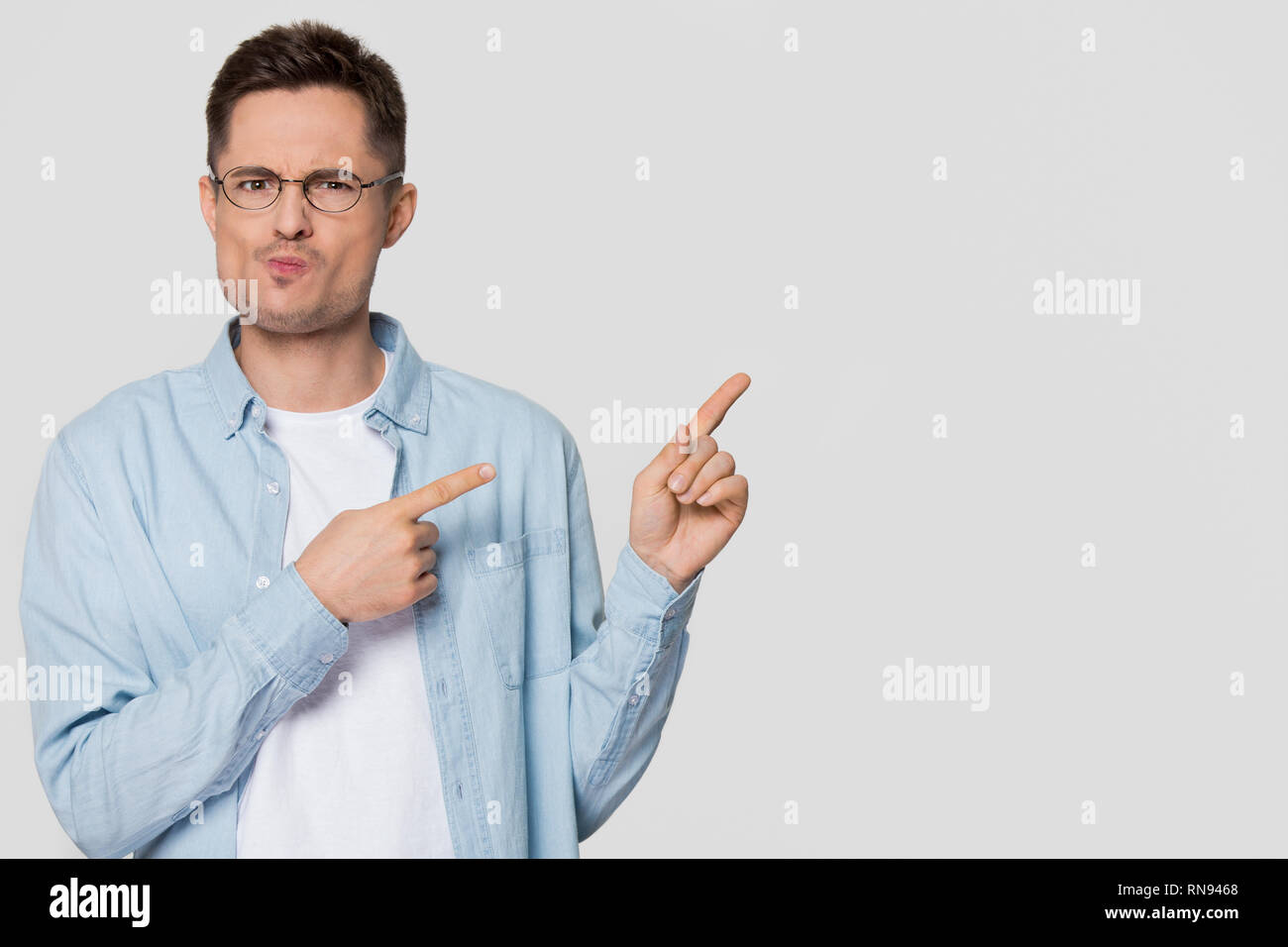 Confused bewildered man pointing fingers at copyspace feeling distrustful - Stock Image