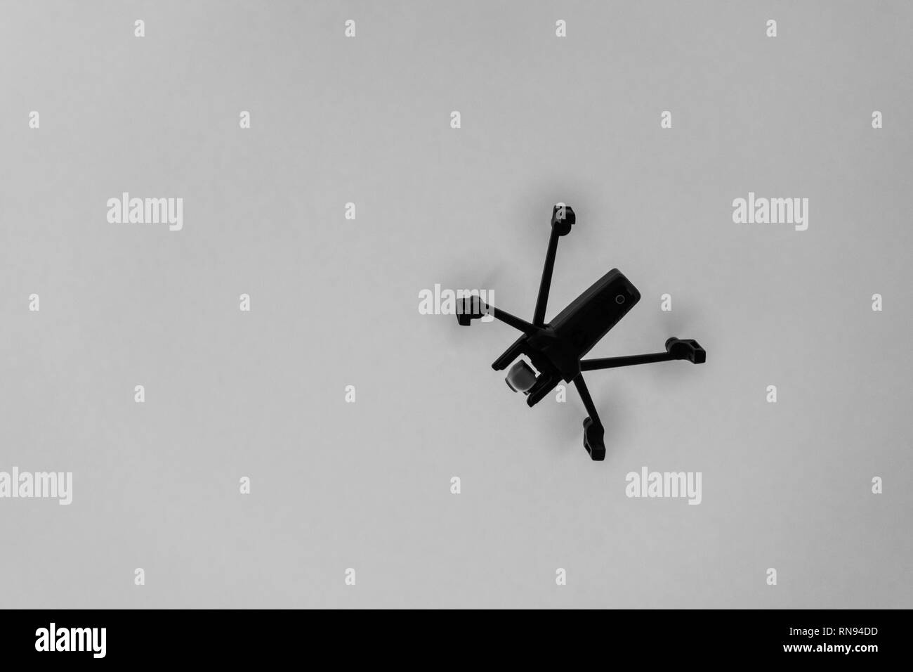 Drone aka unmanned airborne vehicle taking aerial pictures in black and white - Stock Image