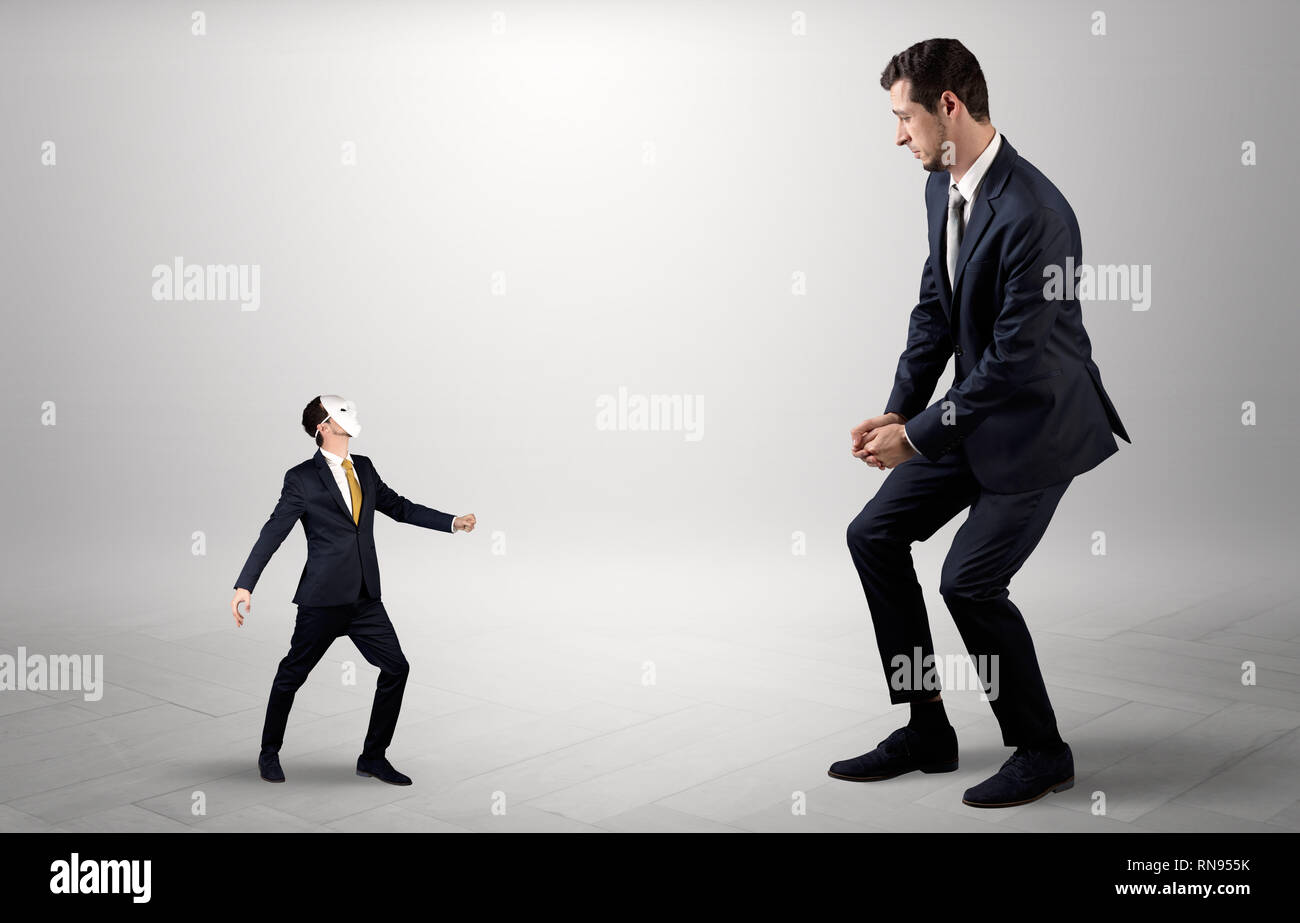 Conflict between small masked businessman and big elegant businessman  - Stock Image