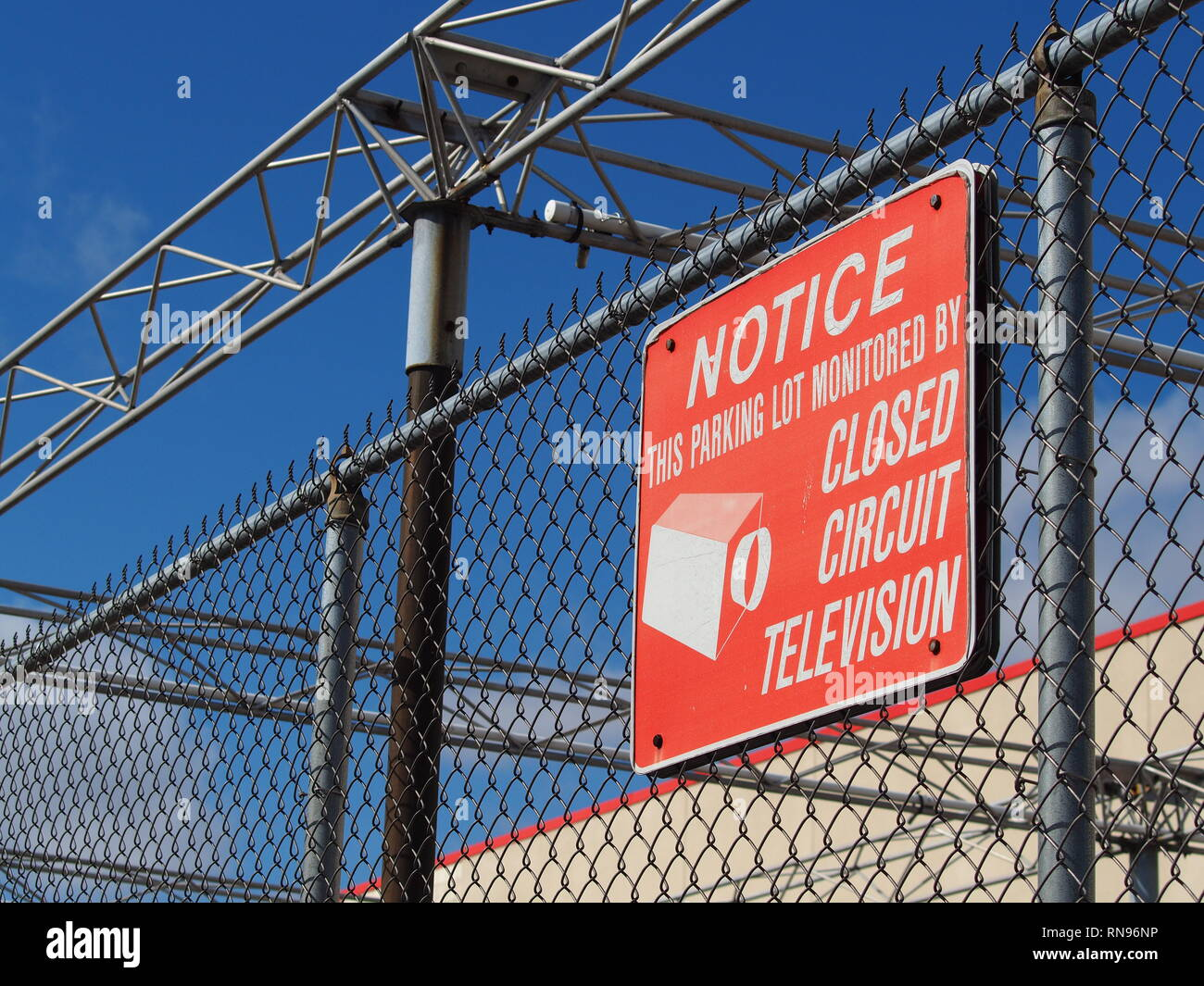 CCT closed circuit television / surveillance camera sign on fence of abandoned  retail store - Stock Image