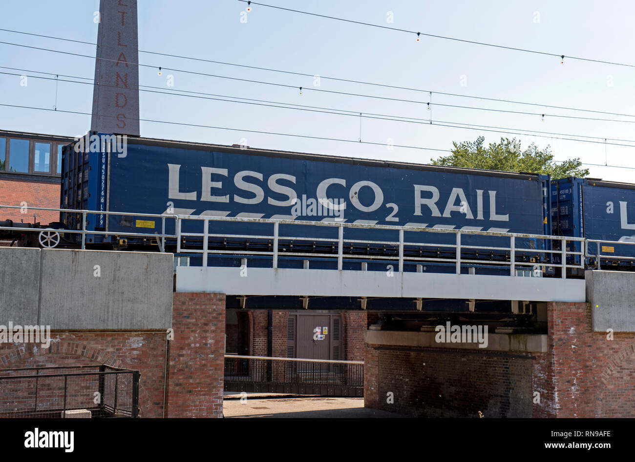 Less C02 Rail printed on the side of a train fright carrage passing through Walthamstow Wetland. - Stock Image