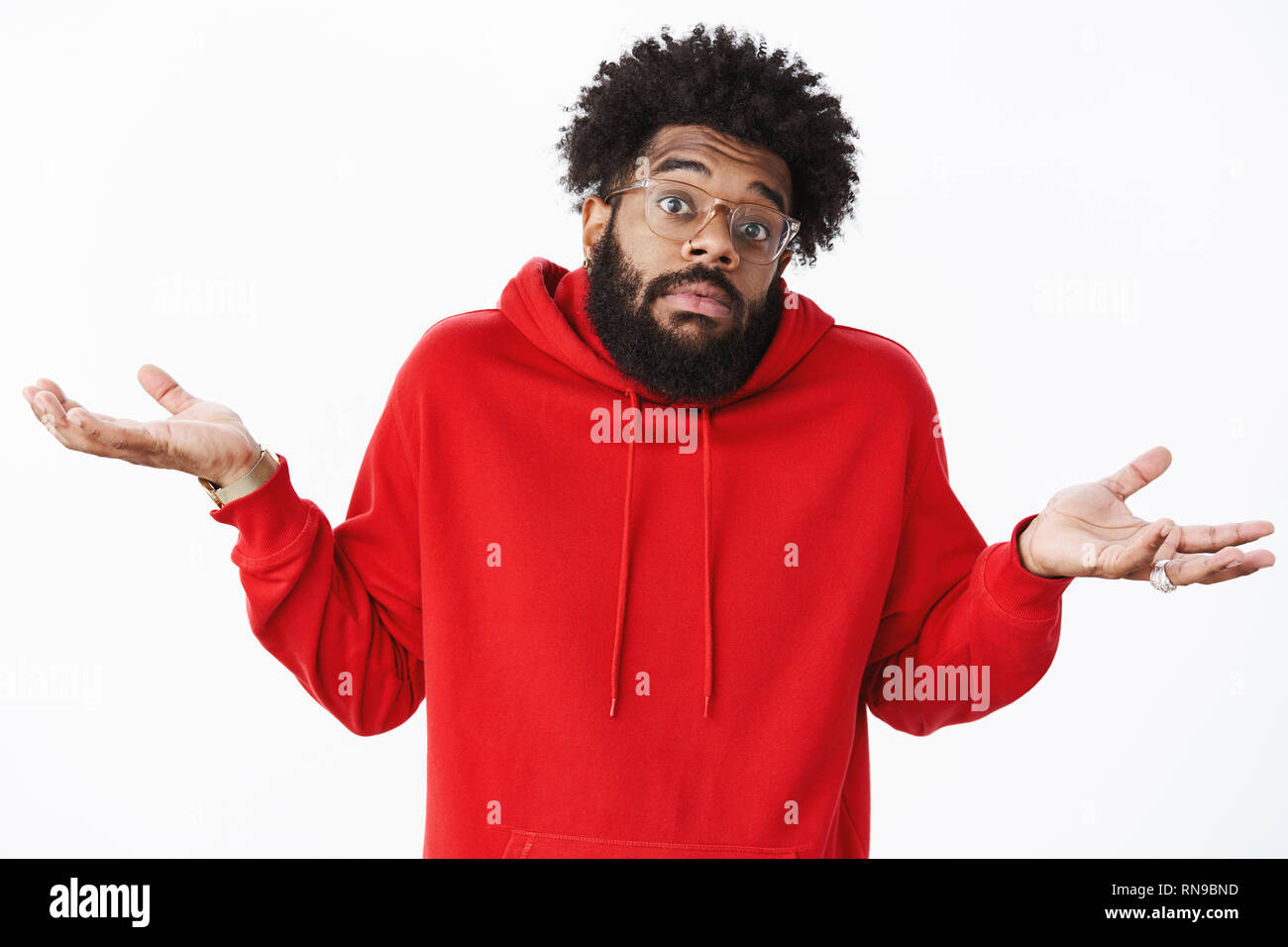 How do I know. Portrait of clueless and unaware unbothered african-american male coworker with beard in glasses and red hoodie, shrugging with hands - Stock Image
