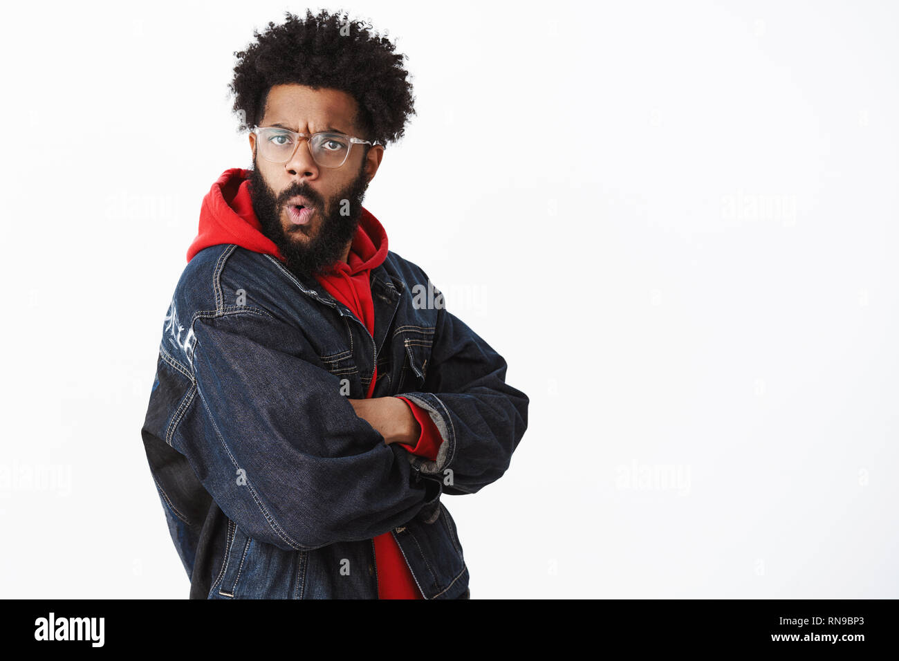 Wow that impressive. Amazed and surprised african american charismatic man with beard, pierced nose and afro hairstyle turning at camera intrigued and - Stock Image