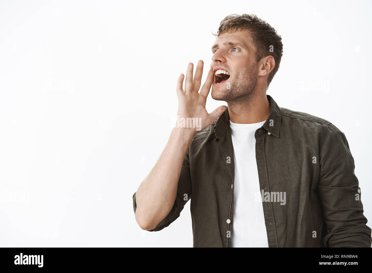 Charming charismatic european blond guy with blue eyes calling someone into distance yelling turning left holding hand near opened mouth as shouting - Stock Image