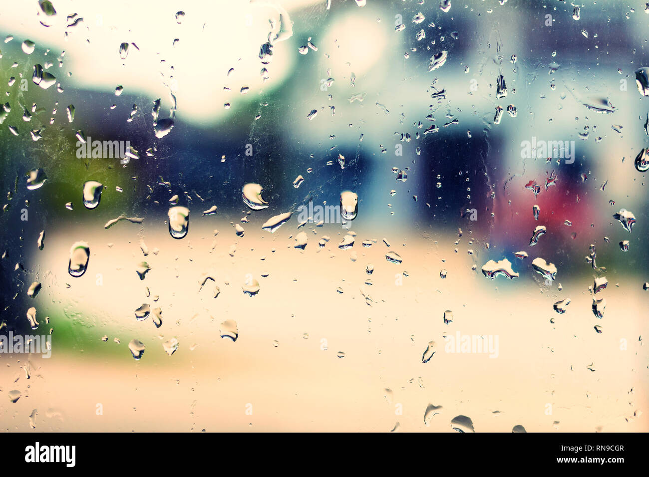 Drops of rain on glass background made with vintage Tones - Stock Image