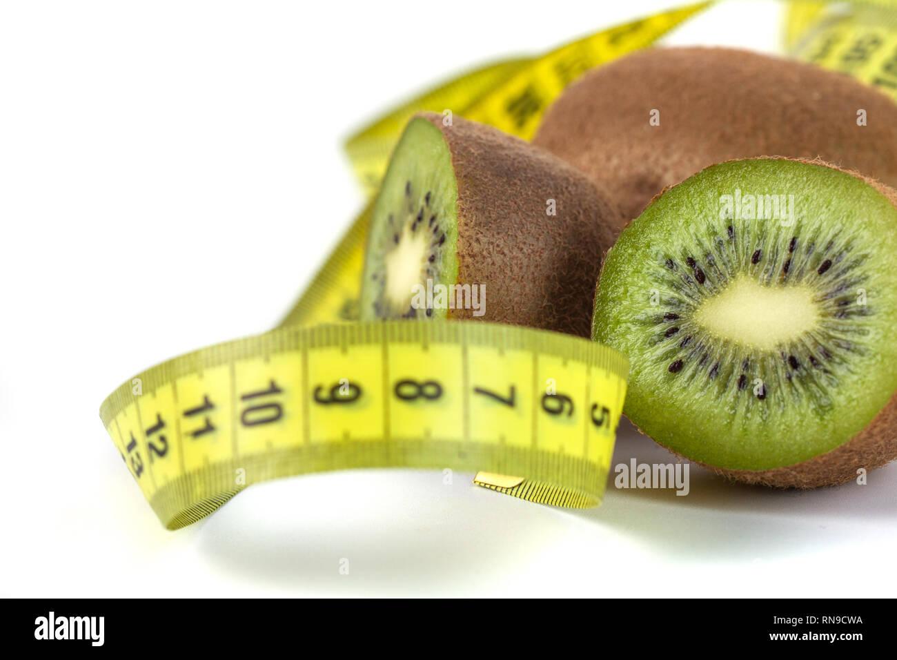 Slaced kiwi fruit and measuring tape isolated on white background. - Stock Image