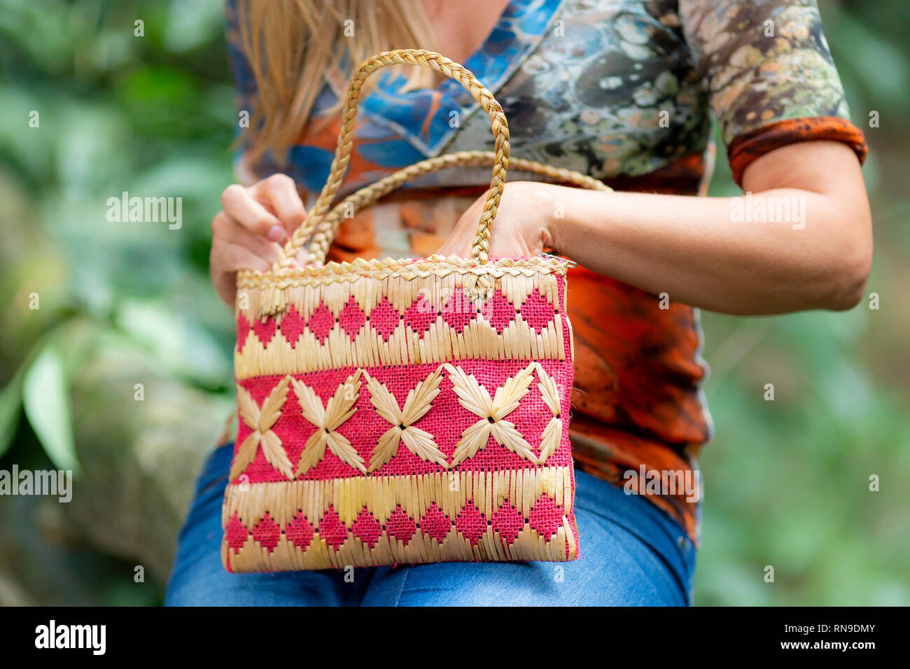 Closeup of the hands of a woman in jeans and colourful top reaching in her handbag that rests on her knees in a natural surrounding in the background Stock Photo