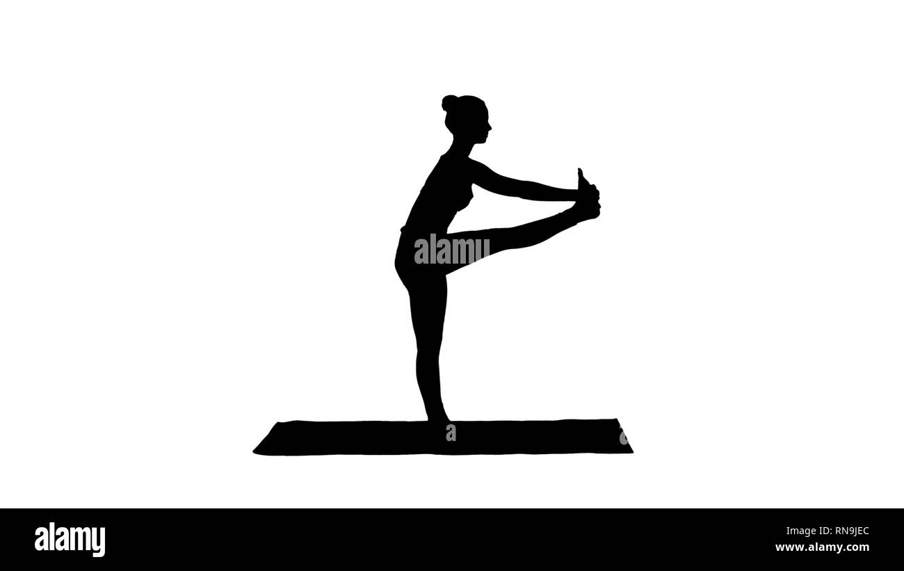 Silhouette Beautiful young fit woman in sportswear doing sport exercise, bending in variation of Utthita Hasta Padangusthasana, Dandayamana - Stock Image