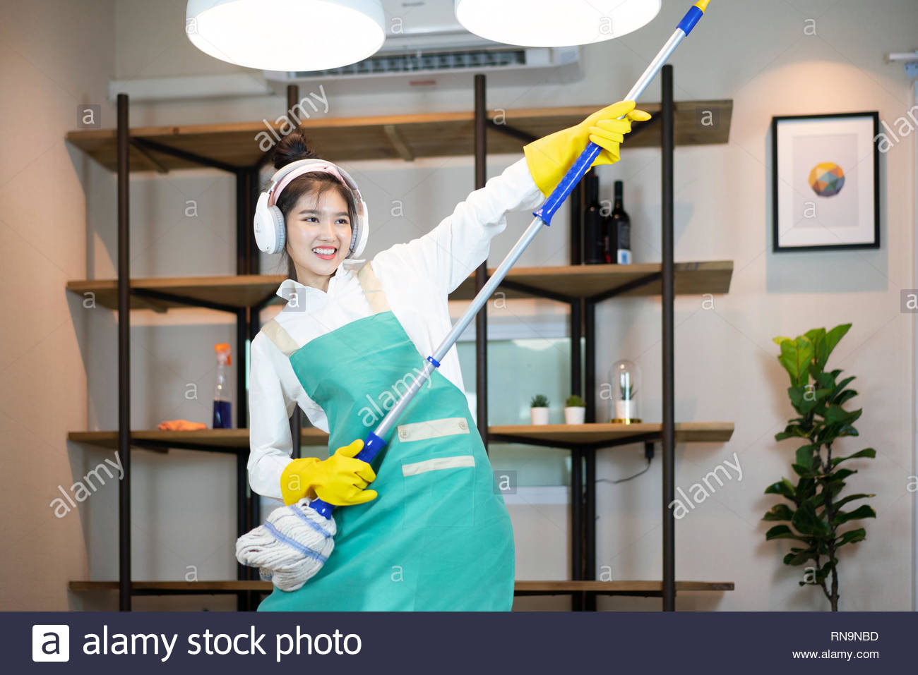 Happy woman cleaning home, singing at mop like at microphone and having fun - Stock Image