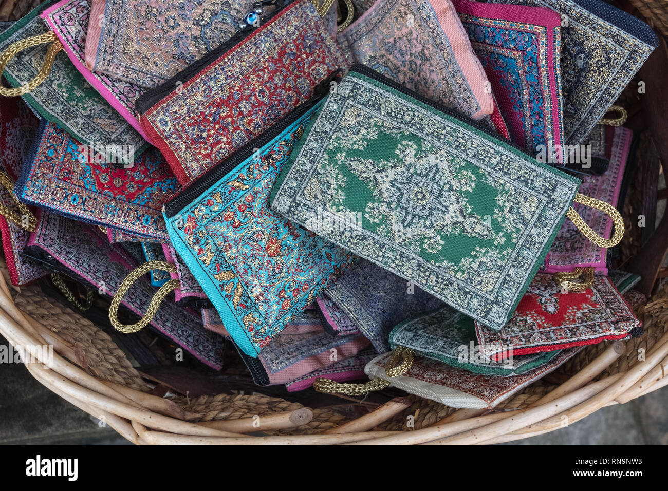 Simple, zippered wallets or purses for sale in souvenir shop basket.  Patterns are delicate, geometric and intricate. - Stock Image