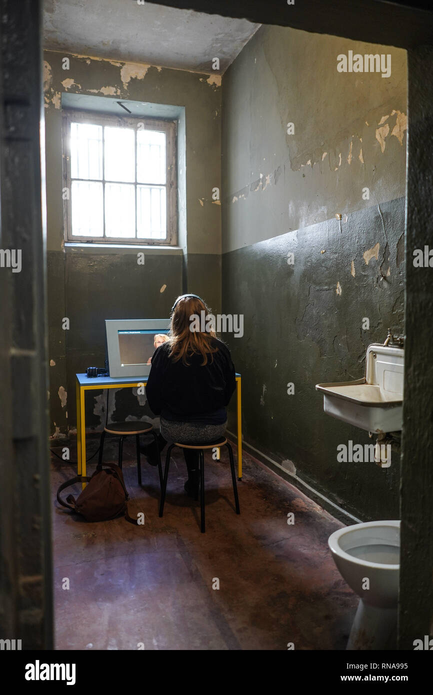 Berlin, Germany. 18th Feb, 2019. At the opening of an extracurricular learning location in a cell of the former GDR police prison in Keibelstraße in Berlin, a schoolgirl learns about the history of the building. According to the Senator, young people there will be able to deal with state arbitrariness and repression in the GDR in the future. Guided tours of the building are also planned for interested visitors. The prison stood empty for years, the use had been struggled for a long time. Credit: Jörg Carstensen/dpa/Alamy Live News - Stock Image