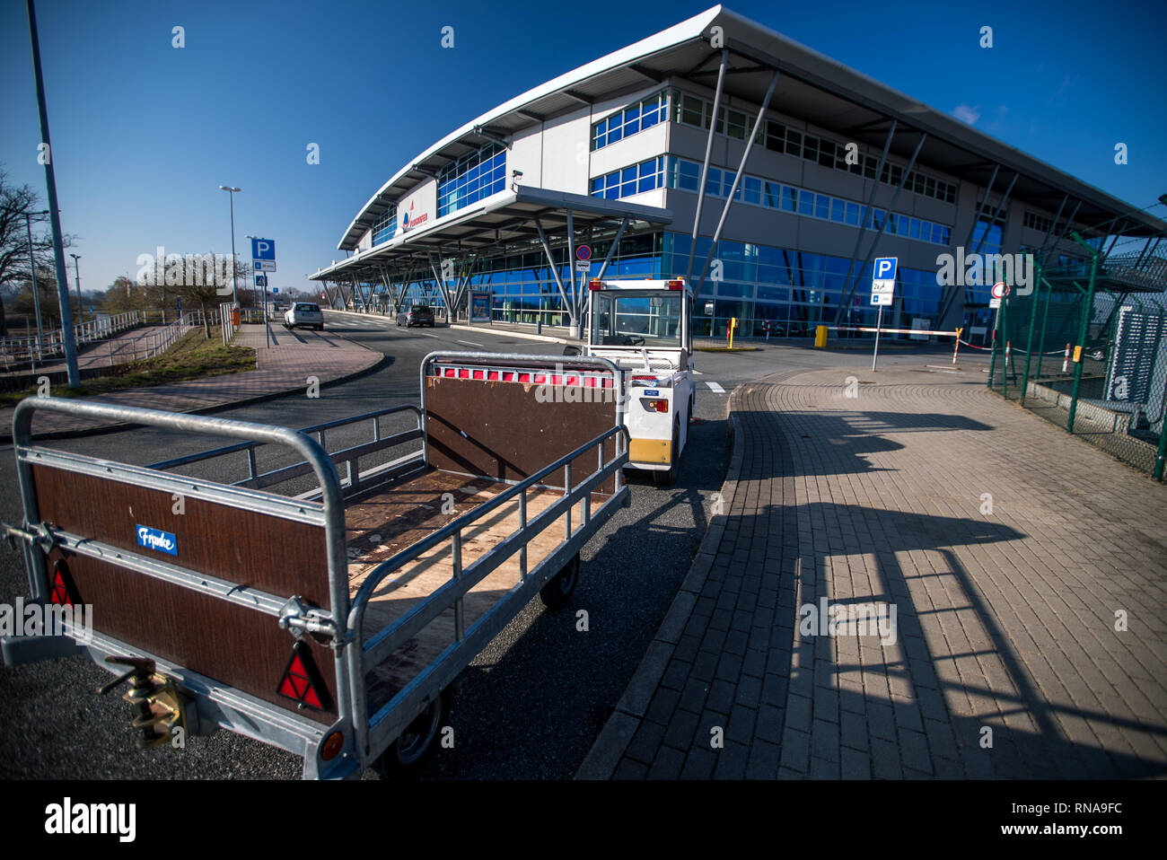 Laage, Germany. 18th Feb, 2019. A transport trailer for suitcases stands in front of the departure hall of Rostock-Laage Airport. Following the insolvency of the British regional airline Flybmi and the holiday airline Germania, the airport's shareholders are discussing the economic situation. For the airport Rostock-Laage the Flybmi flights to Munich were the last regular connections. Credit: Jens Büttner/dpa-Zentralbild/dpa/Alamy Live News - Stock Image