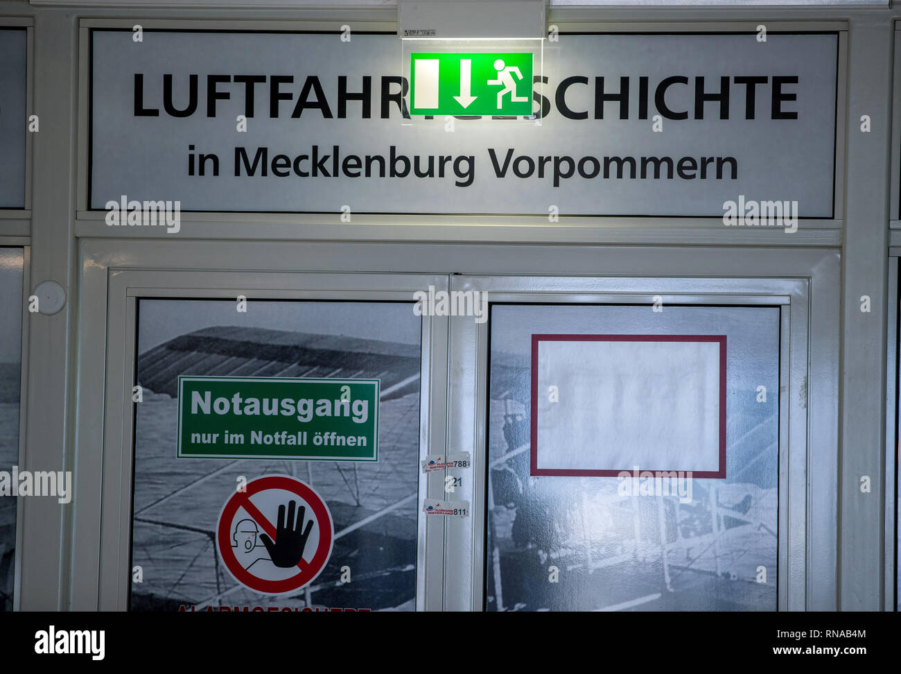 18 February 2019, Mecklenburg-Western Pomerania, Laage: Information signs for the emergency exit hang at the entrance to the aviation history exhibition area in Mecklenburg-Vorpommern at Rostock-Laage Airport. Following the insolvency of the British regional airline Flybmi and the holiday airline Germania, the airport's shareholders are discussing the economic situation. For the airport Rostock-Laage the Flybmi flights to Munich were the last regular connections. Photo: Jens Büttner/dpa-Zentralbild/ZB - Stock Image