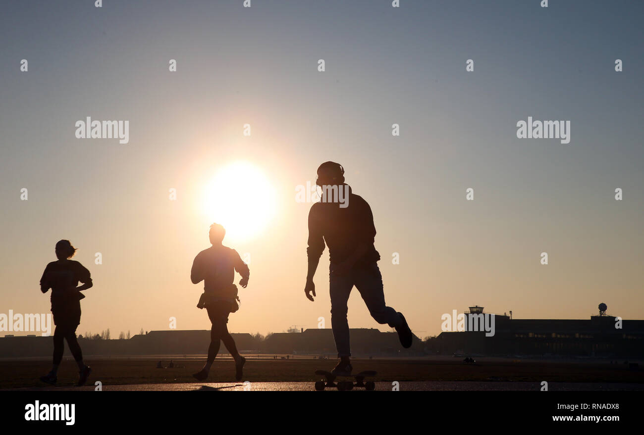 Berlin, Germany. 18th Feb, 2019. In bright sunshine and temperatures around 13 degrees Celsius, people are spending their leisure time on the Tempelhofer Feld in the Tempelhof district. Credit: Wolfgang Kumm/dpa/Alamy Live News - Stock Image