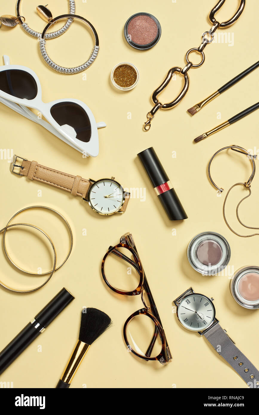 Top view of watches, lipstick, glasses, sunglasses, eyeshadow, blush, cosmetic brushes, bracelets, earrings and mascara Stock Photo