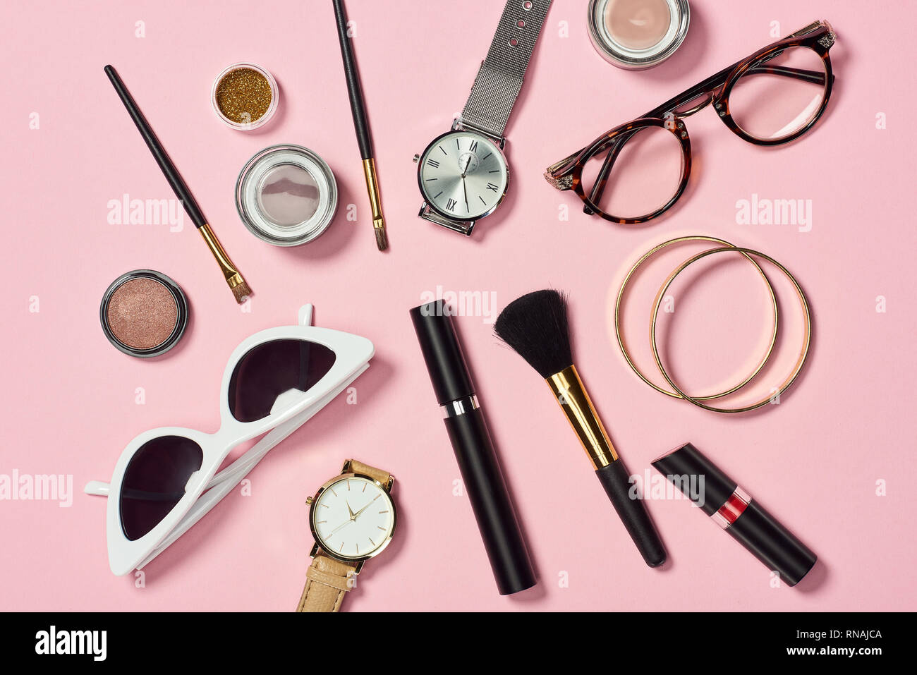 Top view of watches, lipstick, glasses, sunglasses, eyeshadow, blush, cosmetic brushes, bracelets and mascara Stock Photo