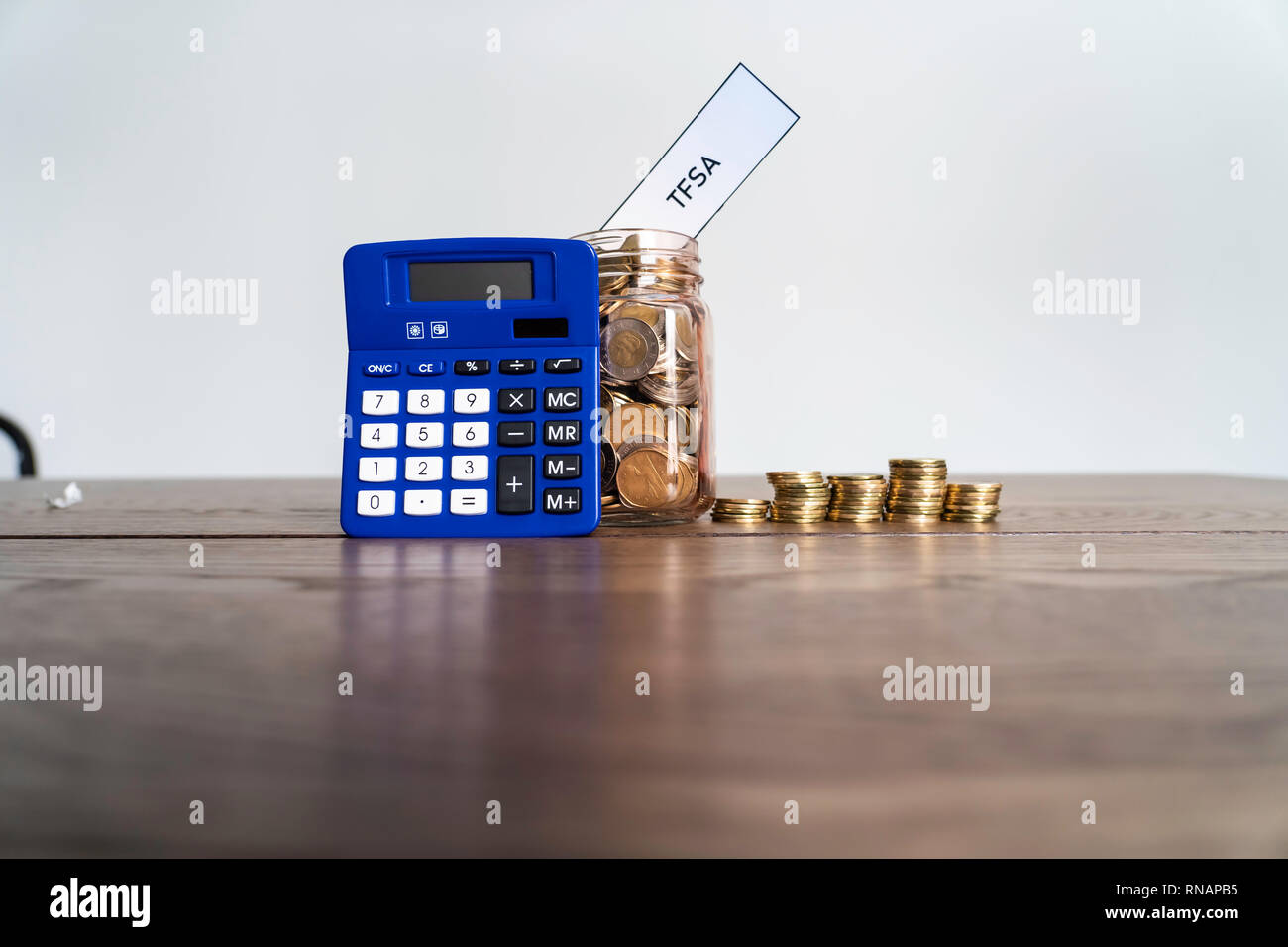 Jar of Coins with calculator showing savings to a Tax Free Savings Account - Stock Image