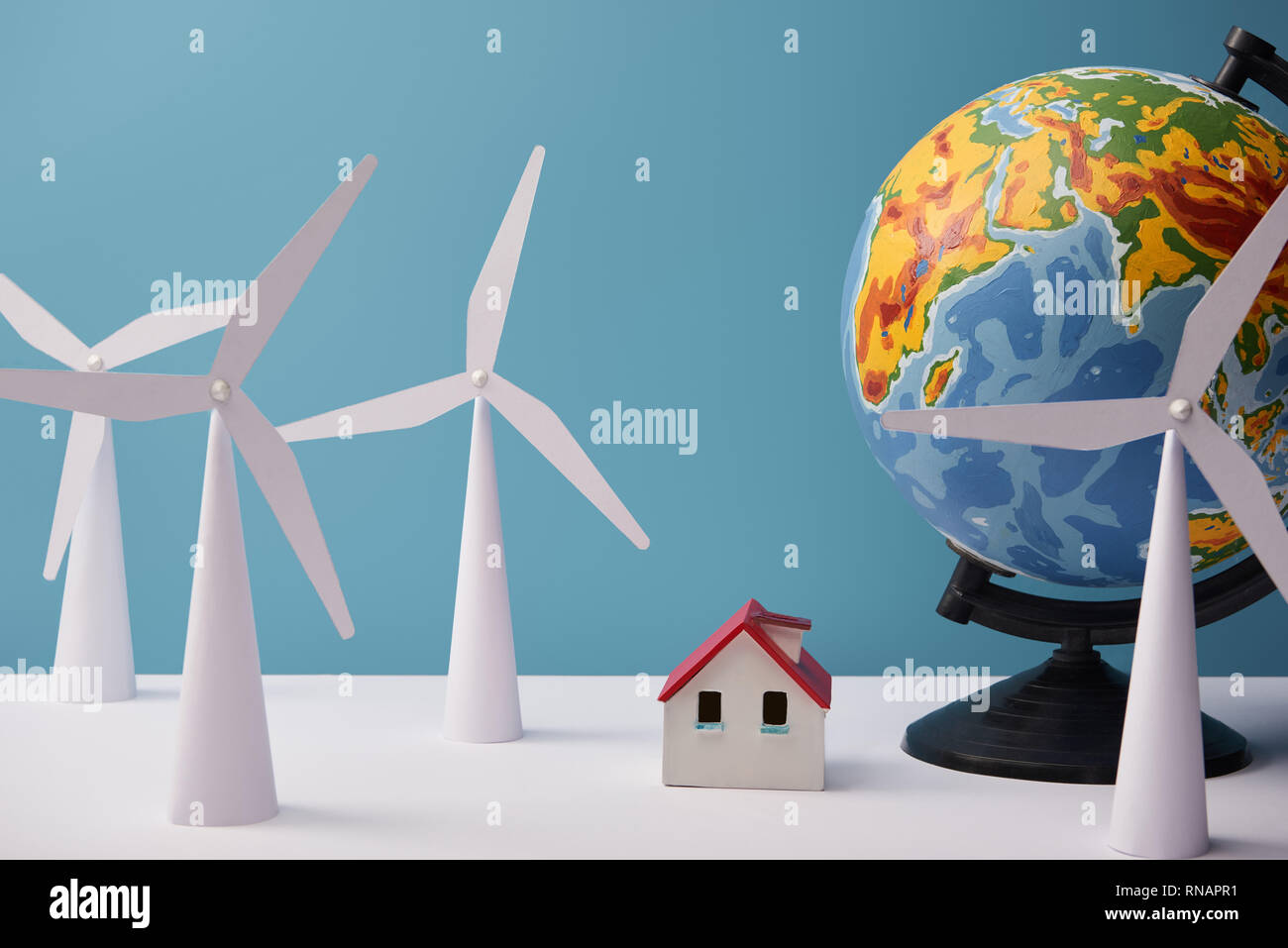 windmill and house models with globe on white table and blue background - Stock Image