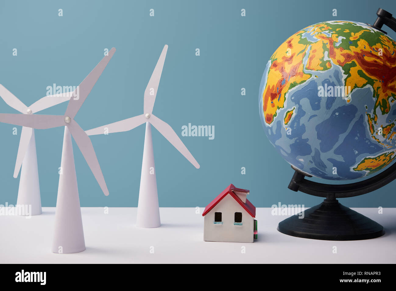 windmill and house models with big globe on white table and blue background - Stock Image