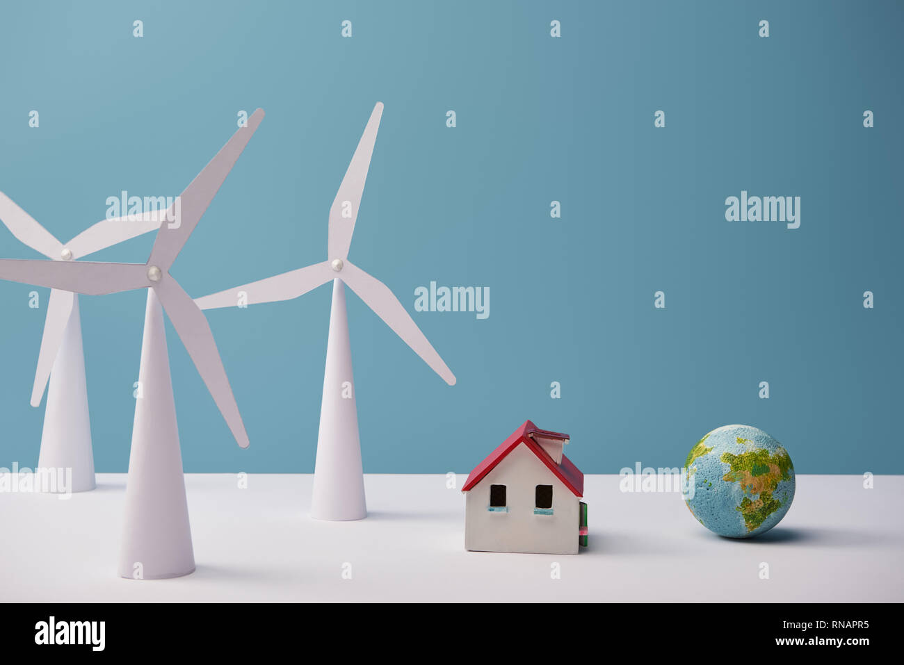 windmill and house models with small globe on white table and blue background - Stock Image