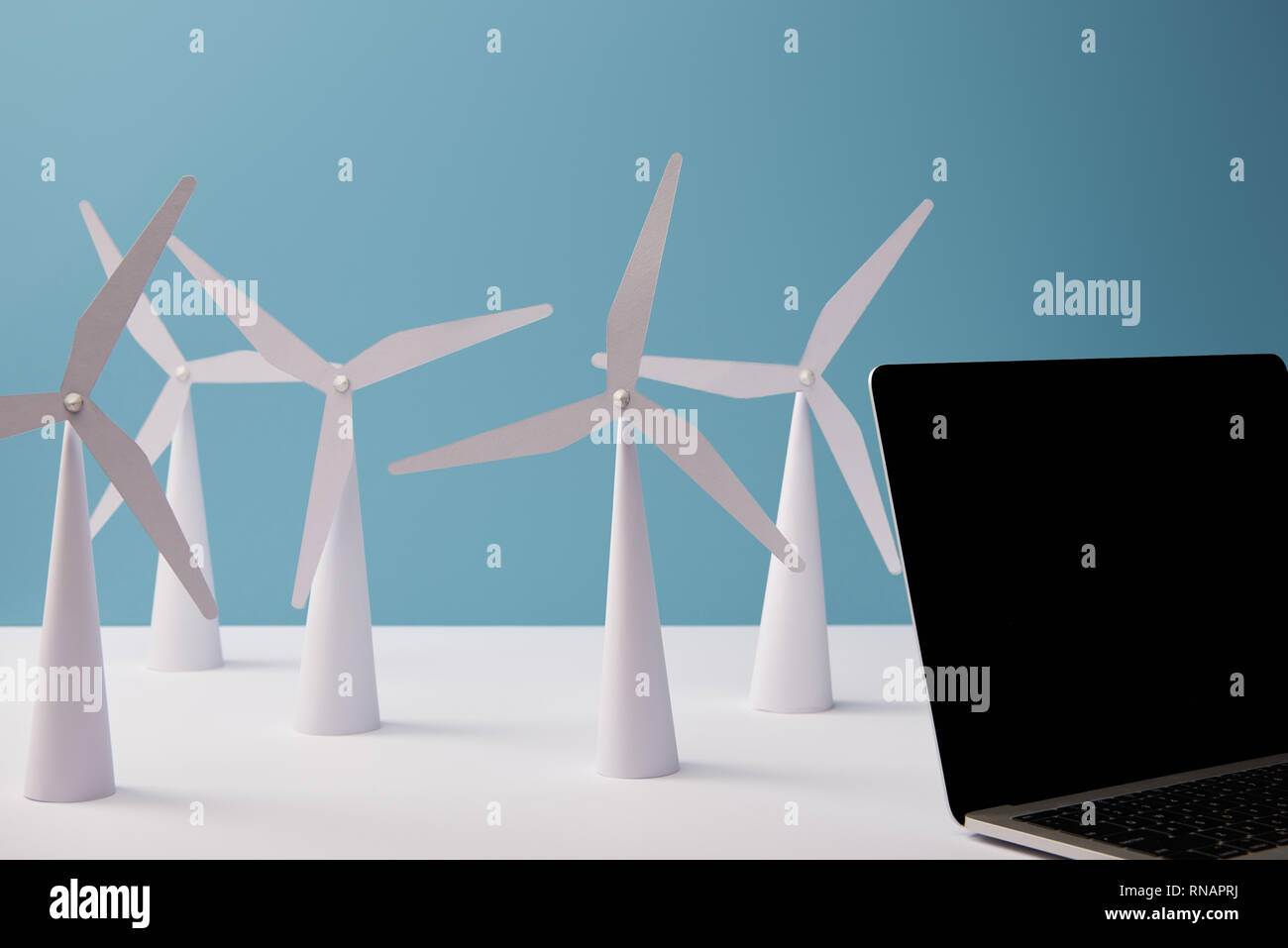 laptop on white table with windmill models on blue background - Stock Image
