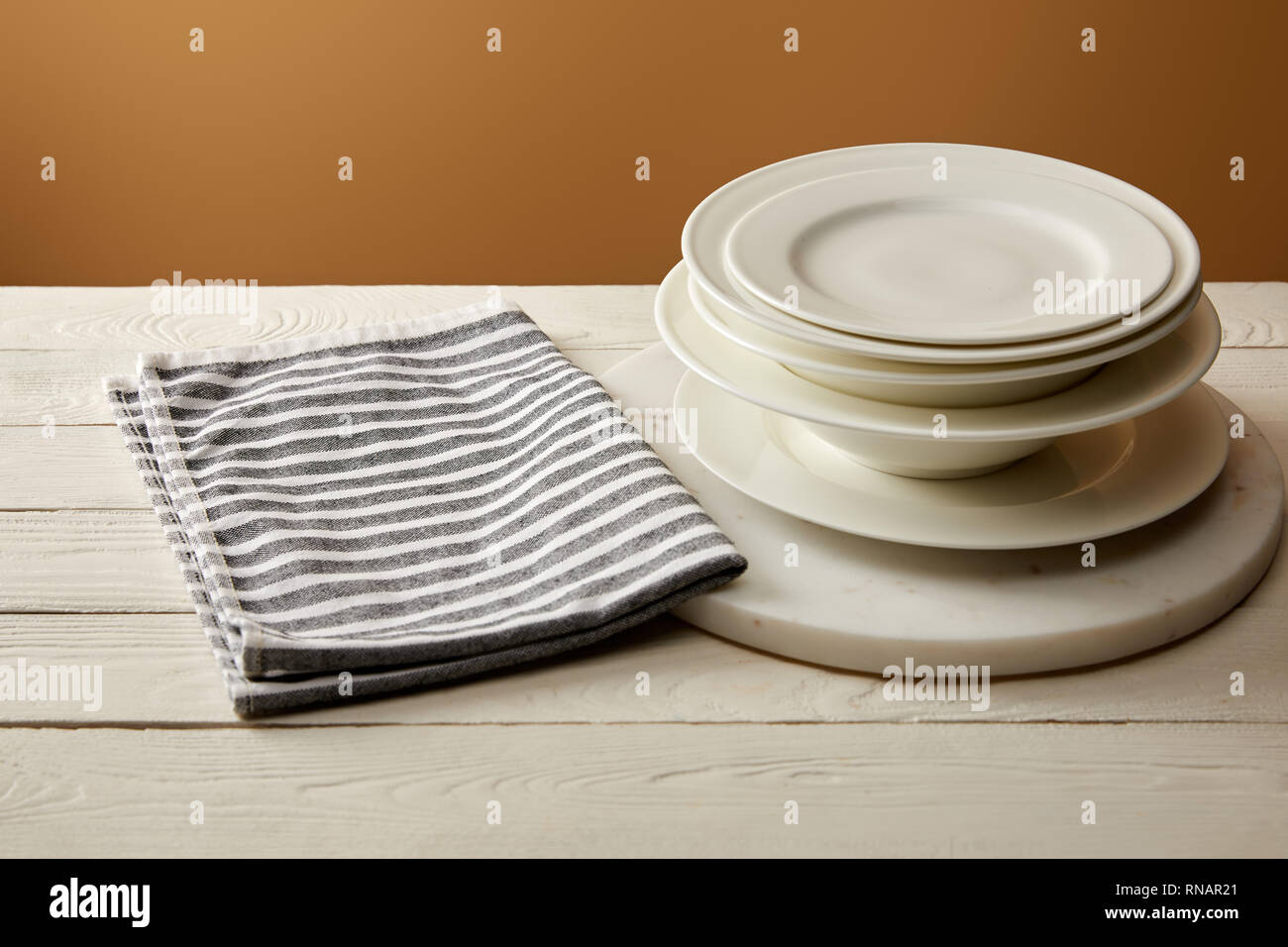 stack of white plates and striped cotton towel on white wooden surface - Stock Image