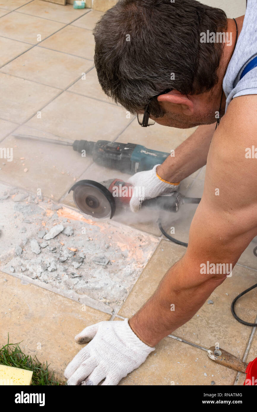 man cut angle grinder concrete in action Dust while grinding tiles, selective focus - Stock Image