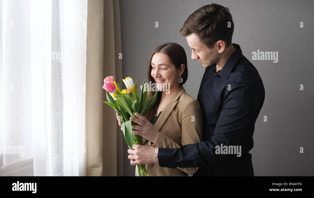 Surprised woman receive tulip flowers from her lover - Stock Image